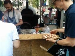 Итальянцы пиццы выпекают в печке на заднем плане